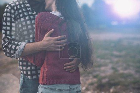Photo pour Jeune couple amoureux s'embrassant à l'extérieur, les arbres et la nature en arrière-plan - image libre de droit