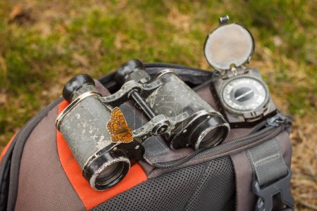 Photo for The butterfly sat down on the binoculars. Tourist equipment. Backpacks with binoculars and old military compass. Time to travel concept. - Royalty Free Image
