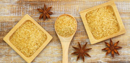 Photo for Brown sugar and star anise on rustic wooden surface - Royalty Free Image
