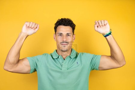 Photo for Young handsome man wearing green casual t-shirt over isolated yellow background showing arms muscles smiling proud - Royalty Free Image