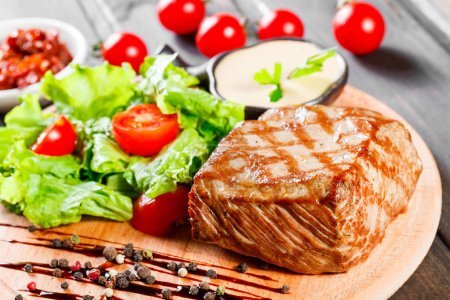 Photo for Grilled steak pork with fresh vegetable salad, tomatoes and sauce on wooden cutting board. - Royalty Free Image