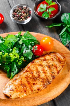 Photo for Grilled chicken fillet with fresh vegetable salad, tomatoes and sauce on wooden cutting board. - Royalty Free Image