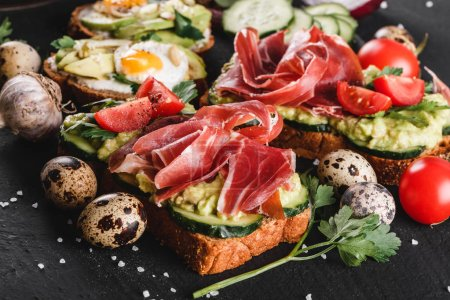 Photo for Various of sandwiches and bruschetta with prosciutto, fried quail egg, avocado, cucumber, tomatoes, spices and greens on black stone background. Clean eating, healthy breakfast. Top view, flat lay - Royalty Free Image
