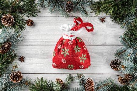 Photo pour Cadre créatif fait de branches d'arbres de Noël et des pommes de pin sur un fond en bois blanc avec sac de Noël. Thème de Noël et du nouvel an. Vue plate Lapointe, top - image libre de droit
