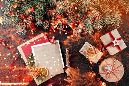 Photo pour Lettre de Noël pour le Père Noël sur fond sombre avec des cadeaux, branches de sapin, cônes de pin. Noël et bonne année thème, bokeh, étincelle, lueur. Couché plat, vue du dessus - image libre de droit