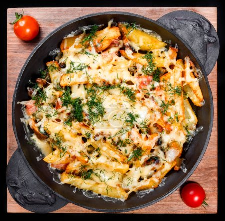 Roasted or baked potato in frying pan with tomatoes, herbs and cheese on wooden board, isolated on black background, homemade food. Top view