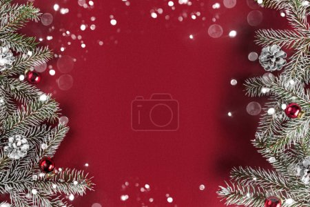 Photo for Creative layout frame made of Christmas fir branches, pine cones, gifts, red decoration on red background. Xmas and New Year theme, bokeh, glowing. Flat lay, top view - Royalty Free Image
