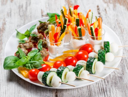 Photo for Appetizer canape with chopped vegetables and sesame on plate over rustic background. Delicious snacks, bruschetta, antipasti on party or picnic time - Royalty Free Image