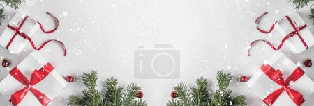 Photo for Creative frame made of Christmas fir branches on white paper background with red decoration, gift boxes. Xmas and New Year theme. Flat lay, top view - Royalty Free Image