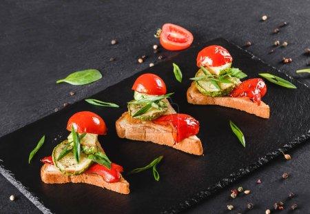 Vorspeise Bruschetta mit Gemüse, Tomaten und Gewürzen auf schwarzem Schieferbrett vor schwarzem Steinhintergrund. gesundes Ernährungskonzept.