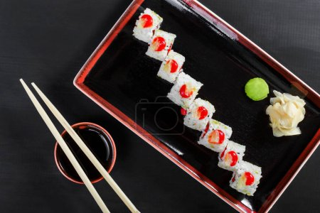 Photo for Sushi Roll - Maki Sushi with sea kale, Crab meat, avocado, cream cheese on dark wooden background. Top view. Japanese cuisine. - Royalty Free Image