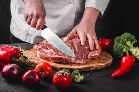 Photo for Chef Butcher cutting pork meat with knife on kitchen, cooking food - Royalty Free Image