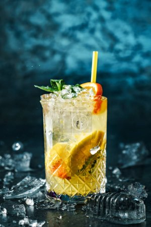 Photo for Fresh lemonade with mint, ginger, orange and ice in glass jar on the dark blue background. Summer cold drink and cocktail - Royalty Free Image