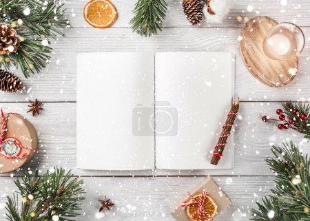Photo pour Mise en page créative faite de branches d'arbre de Noël avec livre de vacances, crayon, cônes de pin, cadeaux sur fond blanc. Noël et bonne année thème, bokeh, étincelle, lueur. Couché plat, vue du dessus - image libre de droit