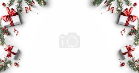 Photo pour Cadre créatif en branches de sapin de Noël, coffrets cadeaux, décoration rouge, scintillements et confettis sur fond blanc. Noël et Nouvel An vacances, bokeh, lumière. Couché plat, vue du dessus - image libre de droit