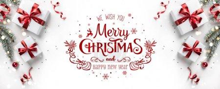 Photo pour Joyeux texte de Noël sur fond blanc avec boîtes cadeaux, rubans, décoration rouge, branches de sapin, bokeh, étincelles et confettis. Carte de voeux de Noël et Nouvel An, bokeh, lumière. Couché plat, vue du dessus - image libre de droit