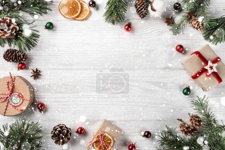 Photo pour Cadre créatif en branches de sapin de Noël sur fond de bois blanc avec décoration rouge, cônes de pin. Thème Noël et Nouvel An. Couché plat, vue du dessus - image libre de droit