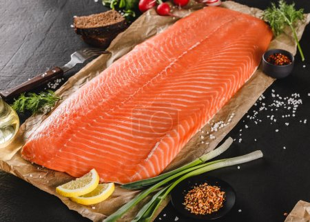 Photo pour Filet de saumon frais, steak de poisson rouge aux épices et citron sur papier artisanal sur fond de pierre sombre. Fruits de mer, gros plan - image libre de droit