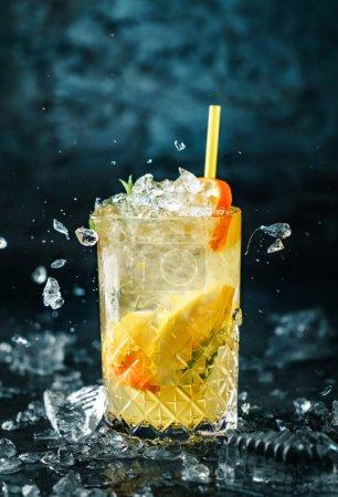 Photo pour Citronnade fraîche avec menthe, gingembre, orange et glace dans un bocal en verre sur fond bleu foncé. Prise de vue studio de boisson en mouvement de gel, glace volante, gouttes dans éclaboussures liquides. Boisson froide et cocktail d'été - image libre de droit