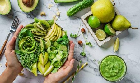 Photo pour Mains tenant salade d'été fraîche saine avec avocat, kiwi, pomme, concombre, poire, légumes verts et sésame avec smoothie sur fond de marbre clair. Nourriture saine, manger propre, salade bol Bouddha, vue sur le dessus - image libre de droit