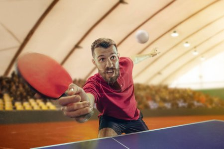 Photo for The table tennis player in motion. Fit young sports man tennis-player in play on sport arena background. Movement, sport game, stobe concepts. Professional. Human emotions, facial expression - Royalty Free Image