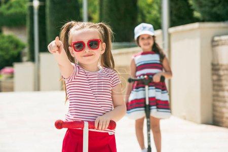 Preschooler girls riding scooter outdoors