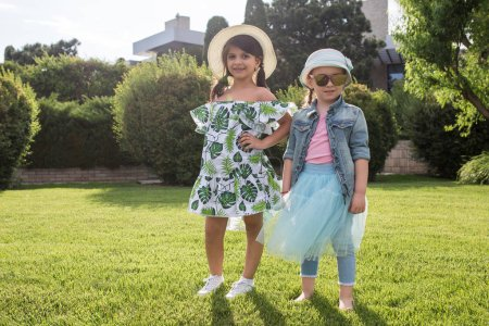 Photo pour Concept de mode pour enfants. Les deux filles posant au parc. Enfants vêtements colorés, style de vie, concepts de couleurs à la mode . - image libre de droit