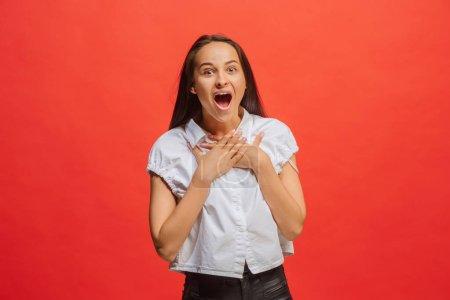 Photo pour Ouah ! Magnifique portrait féminin mi-long isolé sur fond de studio rouge. Jeune femme émotionnelle surprise debout avec la bouche ouverte. Émotions humaines, concept d'expression faciale. Couleurs tendance - image libre de droit