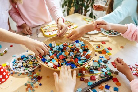 Photo for The mosaic puzzle art for kids, childrens creative game. The hands are playing mosaic at table. Colorful multi-colored details close up. Creativity, childrens development and learning concept - Royalty Free Image