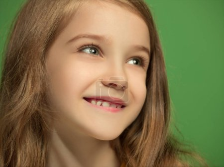 Photo for Happy teen girl standing, smiling isolated on trendy green studio background. Beautiful female portrait. Young satisfy girl. Human emotions, facial expression concept. Front view. - Royalty Free Image