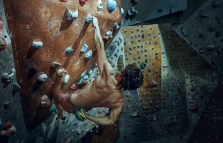 Photo for Free climber young man climbing artificial boulder indoors. Climbing concept and extreme activity. The young fit man on rock - Royalty Free Image