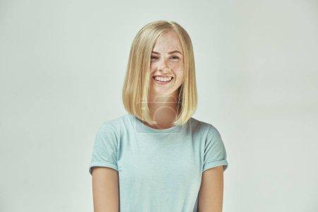 Foto de Feliz pecosa mujer de pie y sonriente aislado sobre fondo gris studio. Hermoso retrato femenino de medio cuerpo. Joven mujer emocional. Las emociones humanas, el concepto de expresión facial. Vista frontal. - Imagen libre de derechos