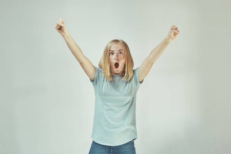 Photo pour J'ai gagné. Gagner le succès femme heureuse célébrant être un gagnant. Image dynamique du modèle féminin à taches de rousseur caucasien sur fond de studio gris. Victoire, concept de délice. Concept d'émotions faciales humaines . - image libre de droit