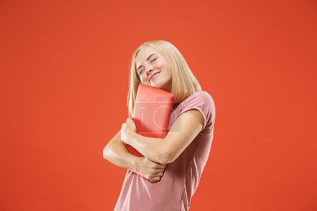 Photo for Businesswoman hugging laptop. Love to computer concept. Attractive female half-length front portrait, trendy red studio backgroud. Young emotional pretty woman. Human emotions, facial expression - Royalty Free Image