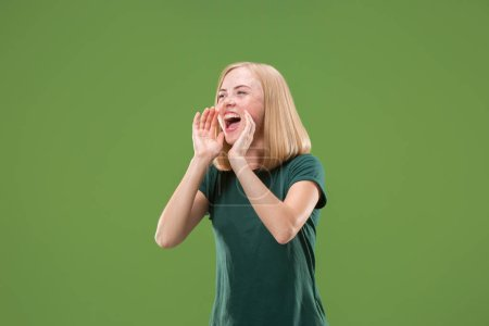 Photo pour Des cris. Pleurer émotionnelle femme en colère criant sur fond de studio vert. Émotionnel, jeune visage. Portrait de femme demi-longueur. Émotions humaines, concept d'expression faciale . - image libre de droit