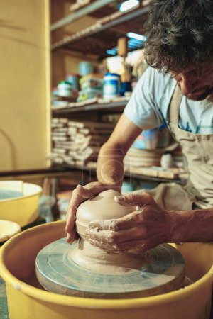Photo for Creating a jar or vase of white clay close-up. Master crock. Man hands making clay jug macro. The sculptor in the workshop makes a jug out of earthenware closeup. Twisted potters wheel. - Royalty Free Image