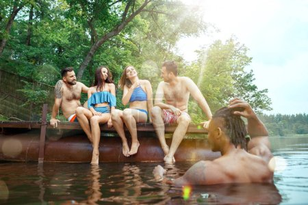 Photo for Enjoying forest party with friends. Group of beautiful happy young men and girls swimming at the river together. Summer, party, adventure, youth, frienship concept - Royalty Free Image