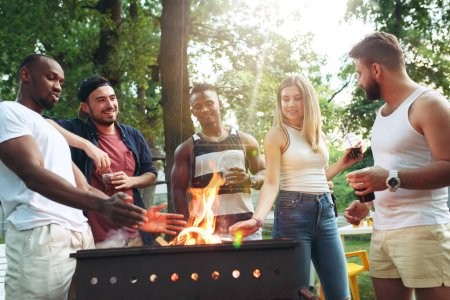 Photo for Group of friends making barbecue in the backyard. concept about good and positive emotions. Enjoying forest party with friends. Summer, party, adventure, youth, frienship concept - Royalty Free Image