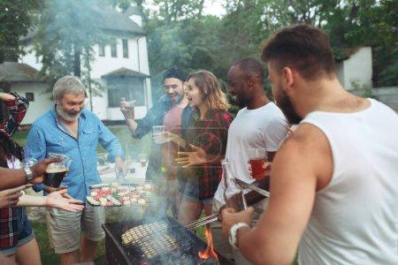 Photo pour Groupe d'amis faisant barbecue à l'arrière-cour. concept sur les émotions bonnes et positives. Profiter d'une fête en forêt avec des amis. Été, fête, aventure, jeunesse, concept d'amitié - image libre de droit