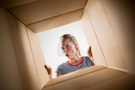Photo for The surprised woman unpacking, opening carton box and looking inside. The package, delivery, surprise, gift, lifestyle concept. Human emotions and facial expressions concepts - Royalty Free Image