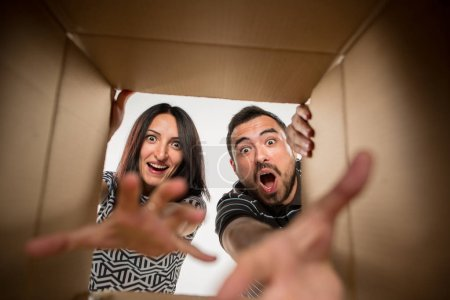 The couple unpacking and opening carton box and looking inside