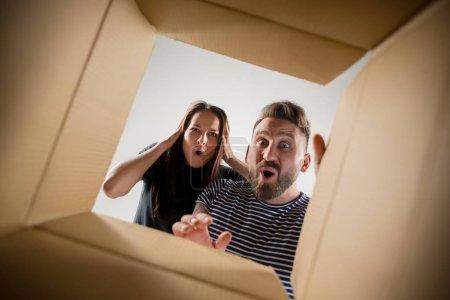 Photo pour L'homme et la femme surpris déballer, ouvrir la boîte en carton et regarder à l'intérieur. Le paquet, livraison, surprise, concept de style de vie cadeau - image libre de droit