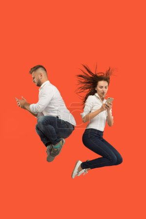 Photo for Always on mobile. Full length of young couple taking phones while jumping against red studio background. Mobile, motion, movement, business concepts - Royalty Free Image