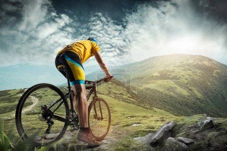 Photo pour Le jeune fit homme en casque de conquérir les montagnes sur une bicyclette. Le concept de vélo, nature, vélo, sport, cycle, extrême, mode de vie, aventure et sport - image libre de droit