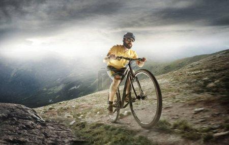 Photo pour Les jeunes hommes en forme dans le casque conquérant des montagnes sur un vélo. Le vélo, la nature, le vélo, le sport, le vélo, l'extrême, le style de vie, l'aventure et le sport - image libre de droit