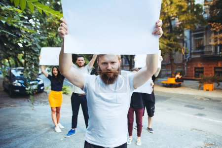 Photo for Group of protesting young people outdoors. The protest, people, demonstration, democracy, fight, rights, protesting concept. The caucasian men and womem holding empty posters or banners with copy - Royalty Free Image