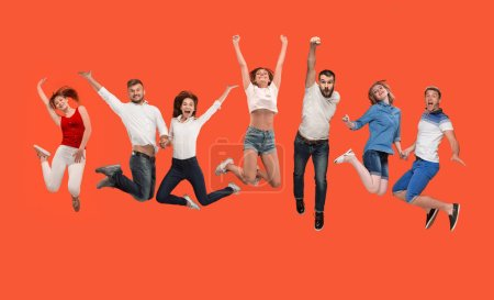 Freedom in moving. young man and women jumping against red background
