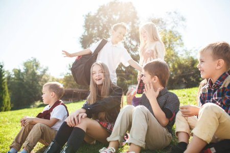 Photo pour Un groupe d'enfants souriants heureux de l'école et de l'âge préscolaire sont assis sur l'herbe verte dans le parc. Enfance, Enfants mode, école, éducation, amis, mode de vie, loisirs, écoliers - image libre de droit