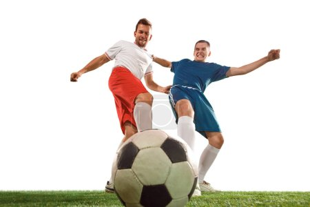 Photo for Football players tackling for the ball over white background. Professional football soccer players in motion isolated white studio background. Fit jumping men in action, jump, movement at game. - Royalty Free Image