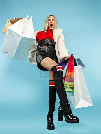 Ganztägiges Porträt einer schönen lächelnden Frau, die mit bunten Einkaufstaschen vor blauem Hintergrund geht